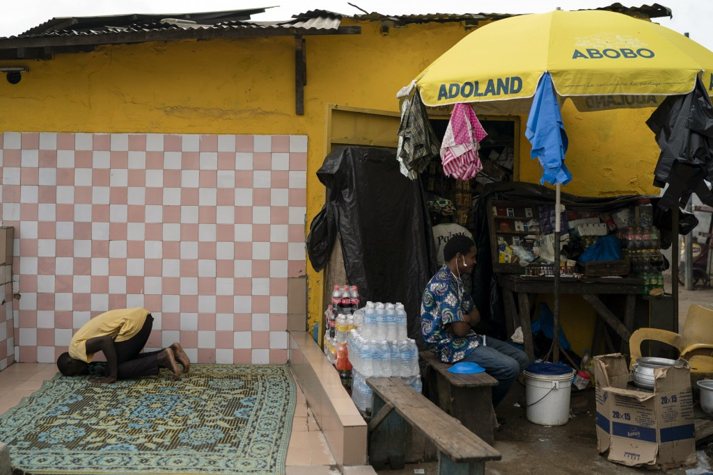 "A Muslim prays next to a kiosk with a parasol reading ""Abobo ADOland"" in reference to the Ivory Coast President Alassane Ouattara, who is known as ADO..."