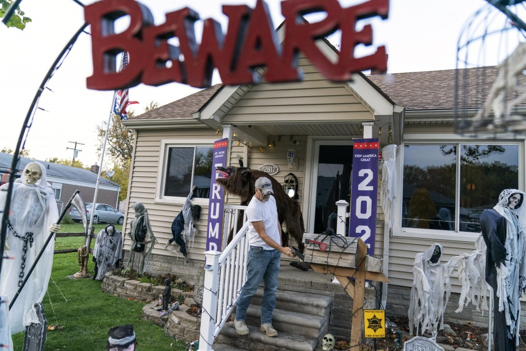 Trump supporter Terry Frandle checks his mailbox in his front yard decorated for Halloween and a Trump reelection campaign in Saint Clair Shores, Mich...