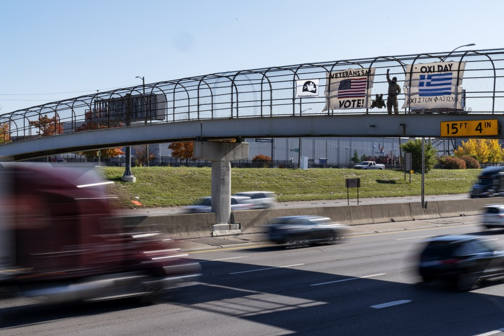An Iraq and Afghanistan war veteran, who did not give his name, stands on a highway overpass with signs encouraging motorists to vote in Hamtramck, Mi...