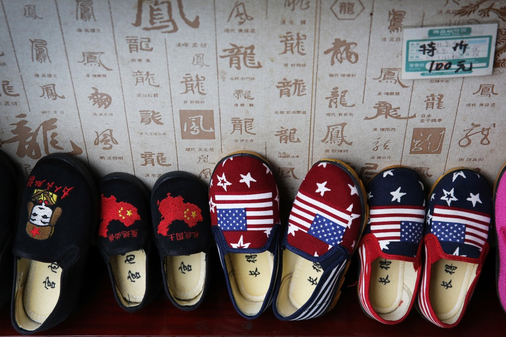 FILE - In this July 13, 2018 file photo, Chinese made children's shoes embroidered with Chinese maps and U.S. flags are on display at a shop in Beijin...
