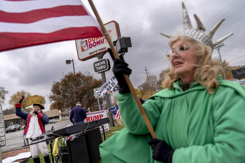 Trump supporters Carol Reed, dressed as the Statue of Liberty, right, and Matthew Woods, dressed as a Continental Army soldier, cheer at an intersecti...