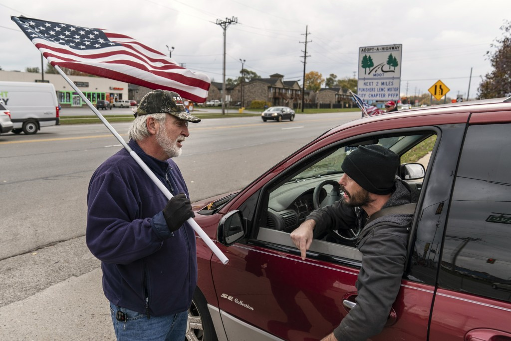 A passing motorist at right argues with Trump supporter Mike Jamerson, left, during a rally at an intersection in Mount Clemens, Mich., Thursday, Oct....
