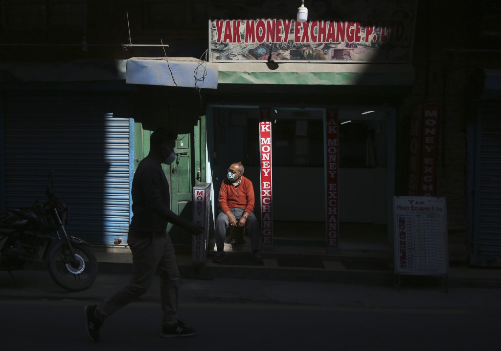 A Nepalese man waits for customers at his money exchange at Thamel, a touristic hub in Kathmandu, Nepal, Monday, Nov. 2, 2020. Nepal has reopened its ...