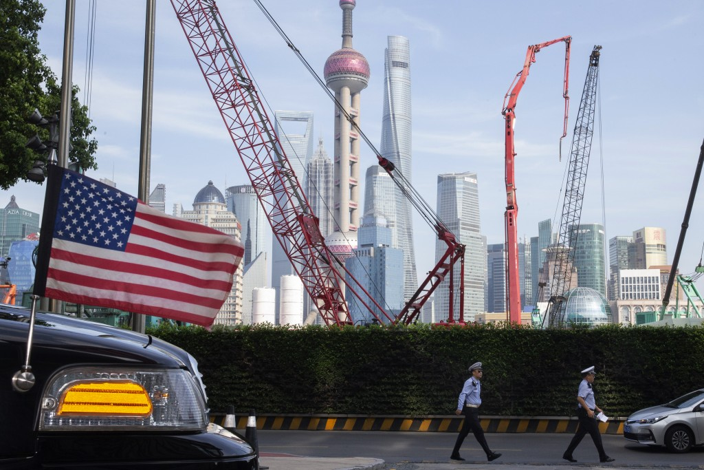 The Shanghai skyline is seen near a U.S. flag on an embassy car outside a hotel where U.S. trade negotiators stayed in Shanghai.