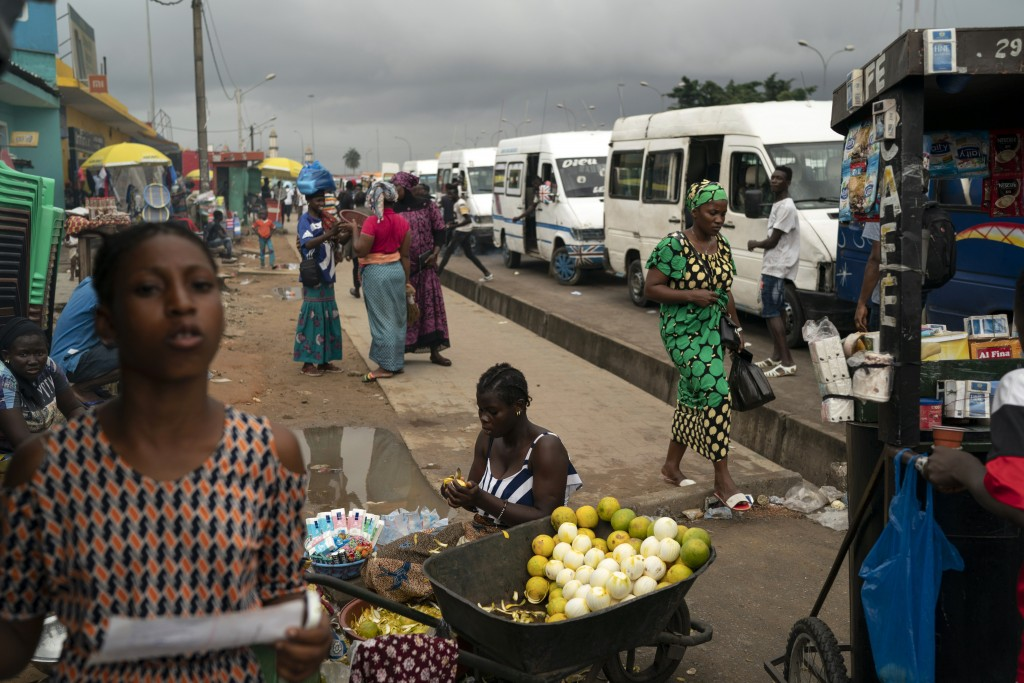 A woman peels oranges to sell on the sidewalk at Abobo neighborhood, a President Alassane Ouattara stronghold, in Abidjan, Ivory Coast, Monday, Nov. 2...