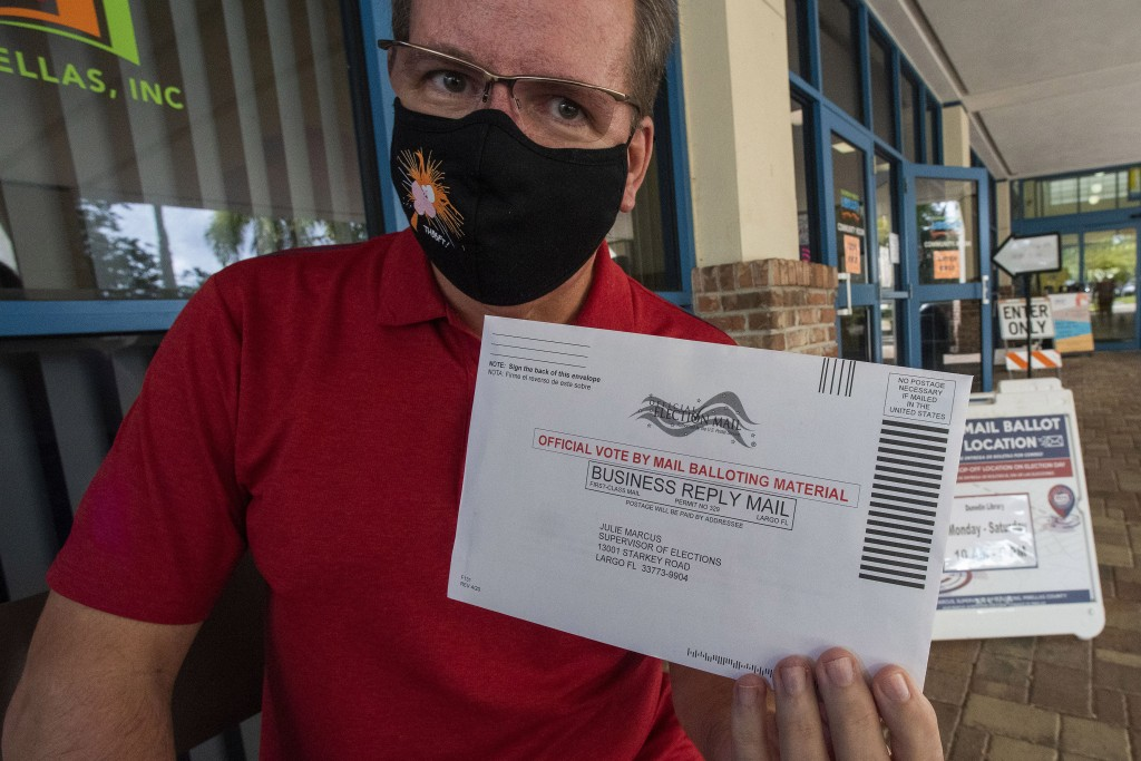 Charles Oppermann holds his vote by mail ballot for Joe Biden outside the drop-off location at the Dunedin Public Library Thursday, Oct. 29, 2020, in ...