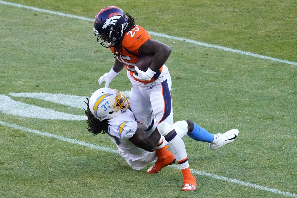 Denver Broncos running back Melvin Gordon (25) is hit by Los Angeles Chargers cornerback Tevaughn Campbell (37) during the first half of an NFL footba...