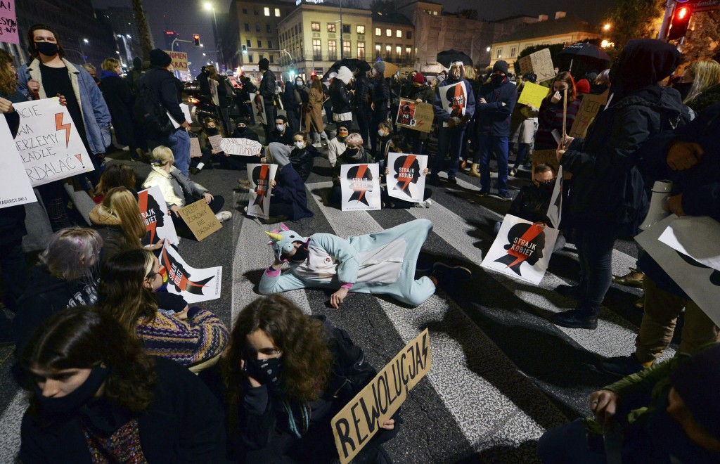Protesters block a crossing in downtown Warsaw, Monday, Nov. 9, 2020, on the 12th straight day of anti-government protests that were triggered by the ...