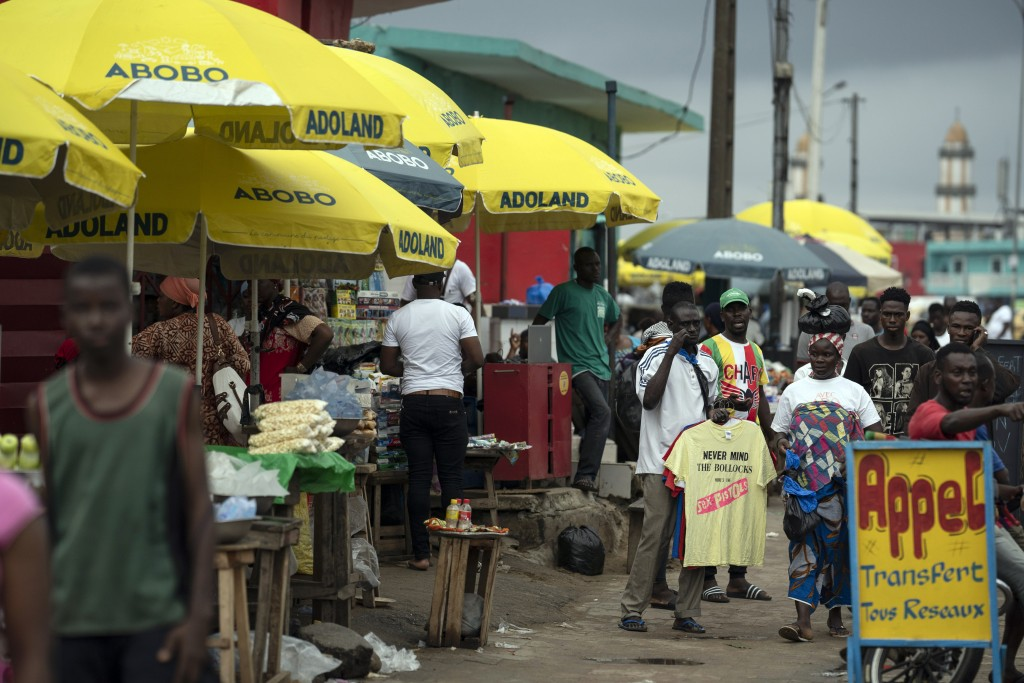 "Street vendors use parasols reading ""Abobo ADOland"" in reference to the Ivory Coast President Alassane Ouattara, who is known as ADO, at Abobo neighbo..."