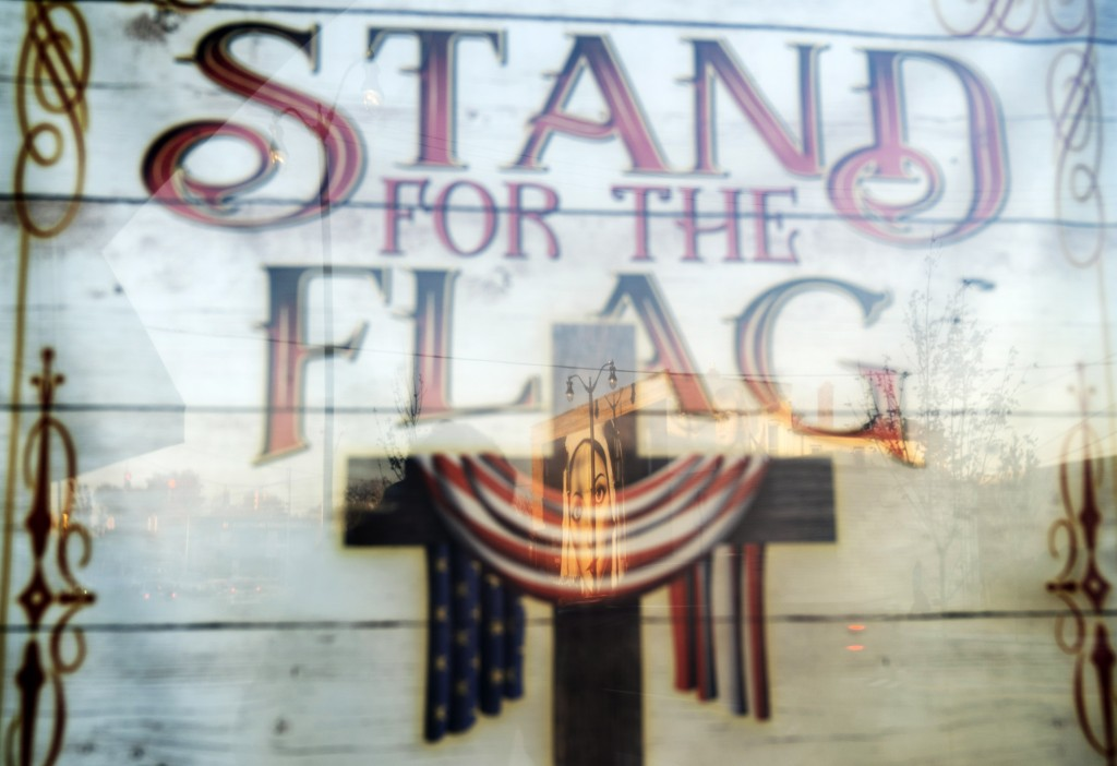 "A mural of the Virgin Mary, painted on the side of a building, is reflected in a poster which reads ""Stand for the Flag, Kneel for the Cross,"" outside..."
