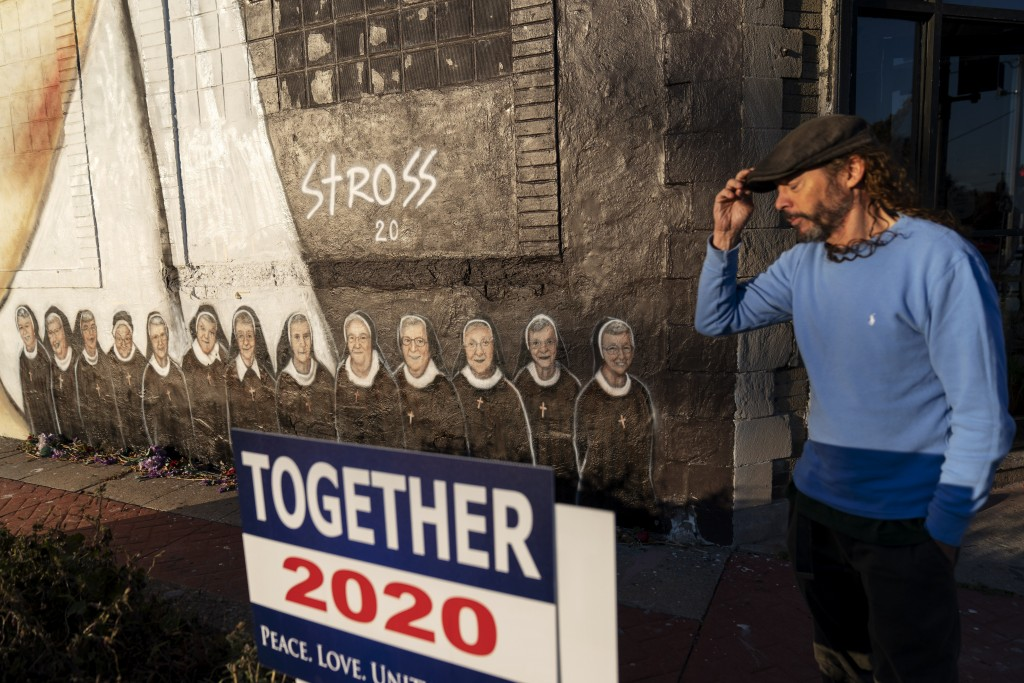 Artist Edward Stross stands next the mural he painted to honor the 13 nuns who died at a local convent from COVID-19, at his studio in Roseville, Mich...