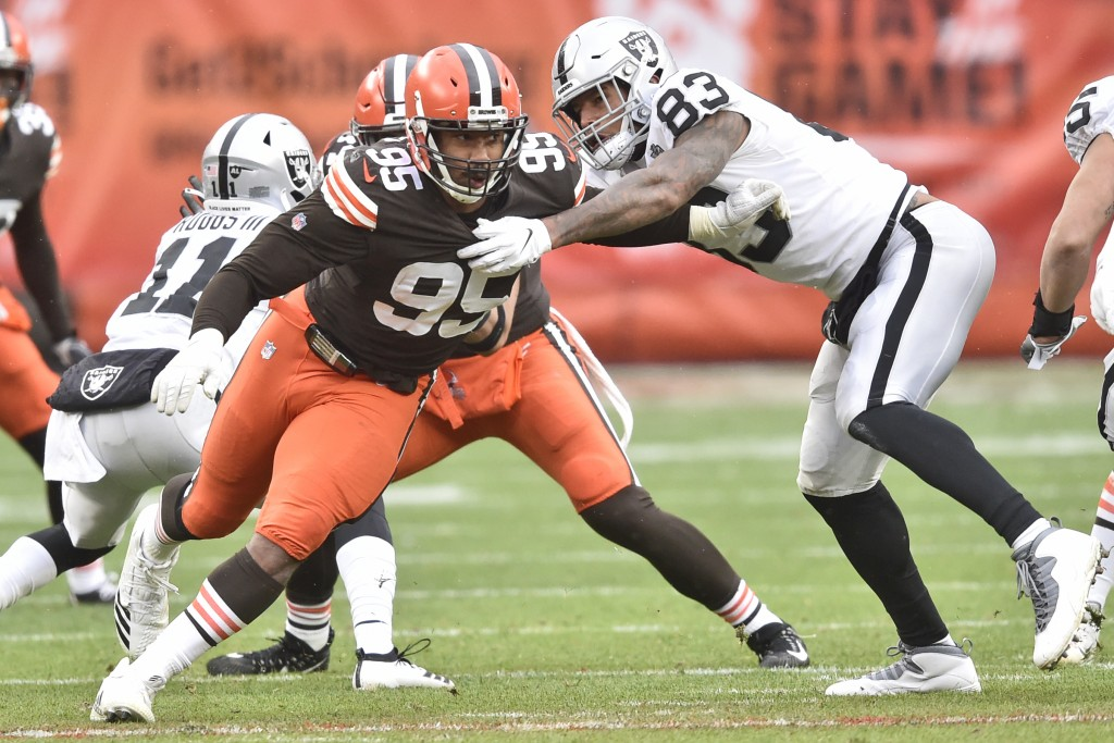 Cleveland Browns defensive end Myles Garrett (95) runs around Las Vegas Raiders tight end Darren Waller (83) during the first half of an NFL football ...