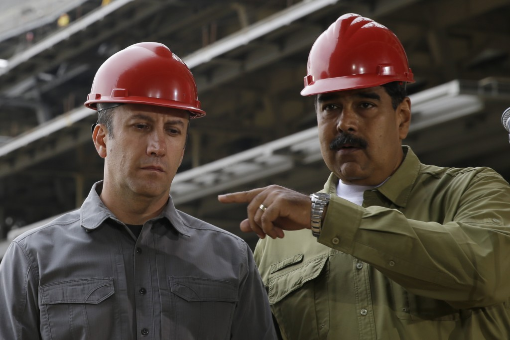 FILE - In this May 19, 2018 file photo, Venezuela's President Nicolas Maduro, right, and then Vice President Tareck El Aissami tour the construction s...