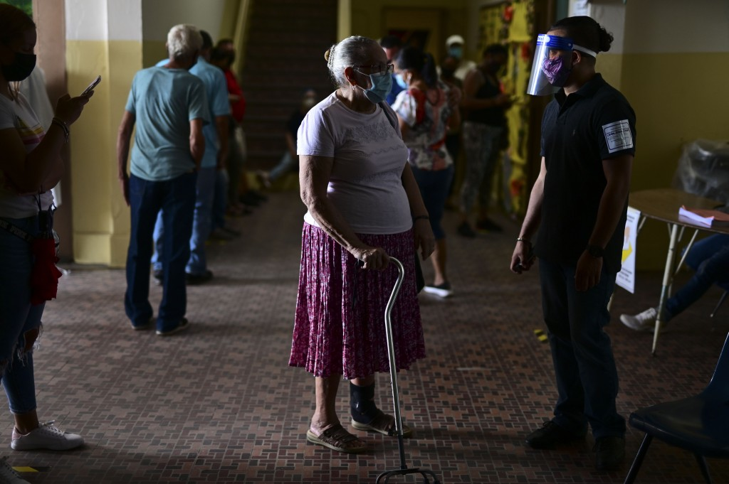 People wait in line to vote during the general election at a voting center set up at the Manuel Gaetan Barbosa School in San Juan, Puerto Rico, Tuesda...