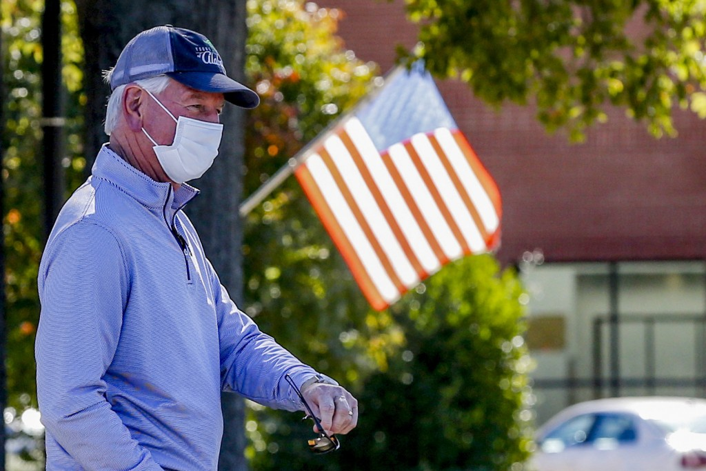 Republican nominee for the Alabama Senate, Tommy Tuberville, stands in a long line waiting to cast his vote on Tuesday, Nov. 3, 2020, in Auburn, Ala. ...