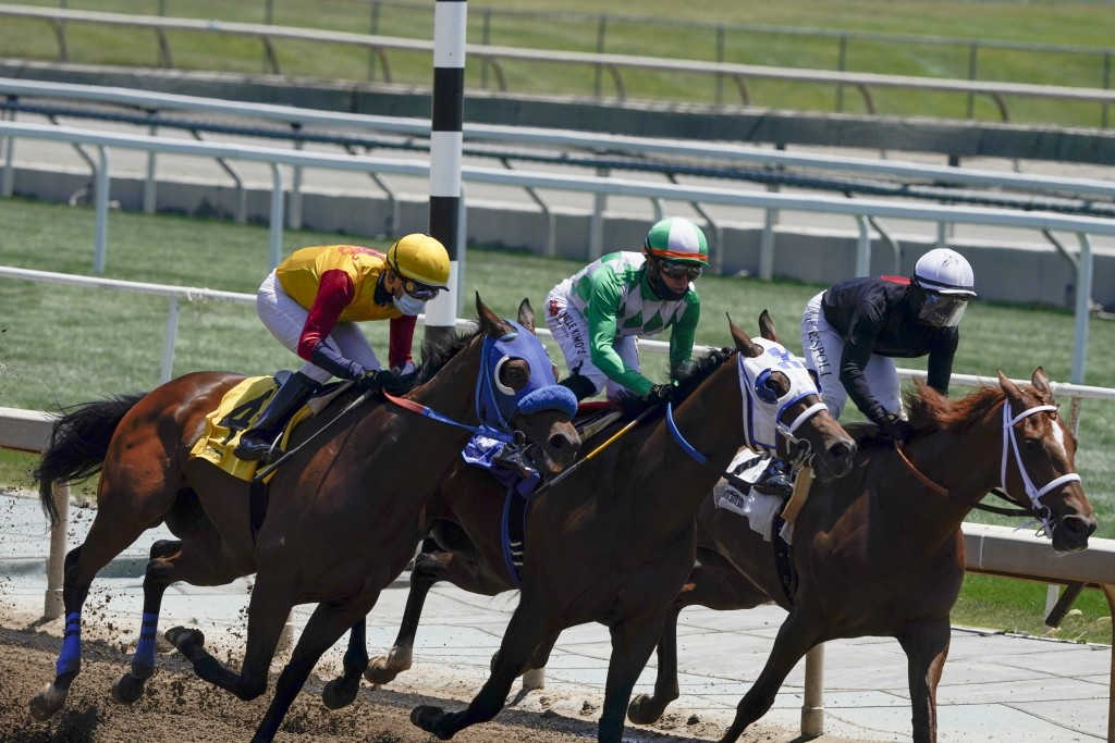 FILE - In this Friday, May 22, 2020, file photo, jockeys wearing face masks ride in the first horse race at Santa Anita in Arcadia, Calif. After a spi...