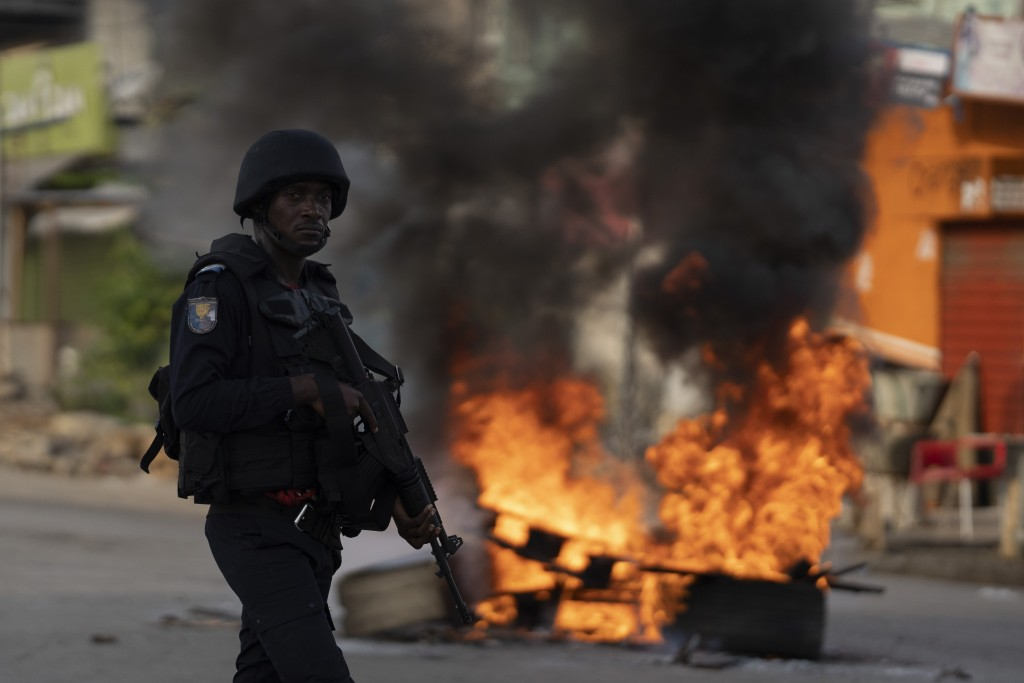 A policeman walks past a burning barricade during a protest after security forces blocked the access to the house of the former president Henri Konan ...