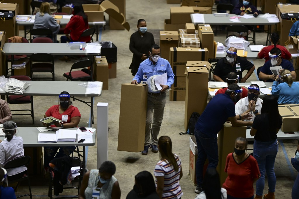 Officials count early votes at the Roberto Clemente Coliseum where social distancing is possible amid the COVID-19 pandemic, during general elections ...
