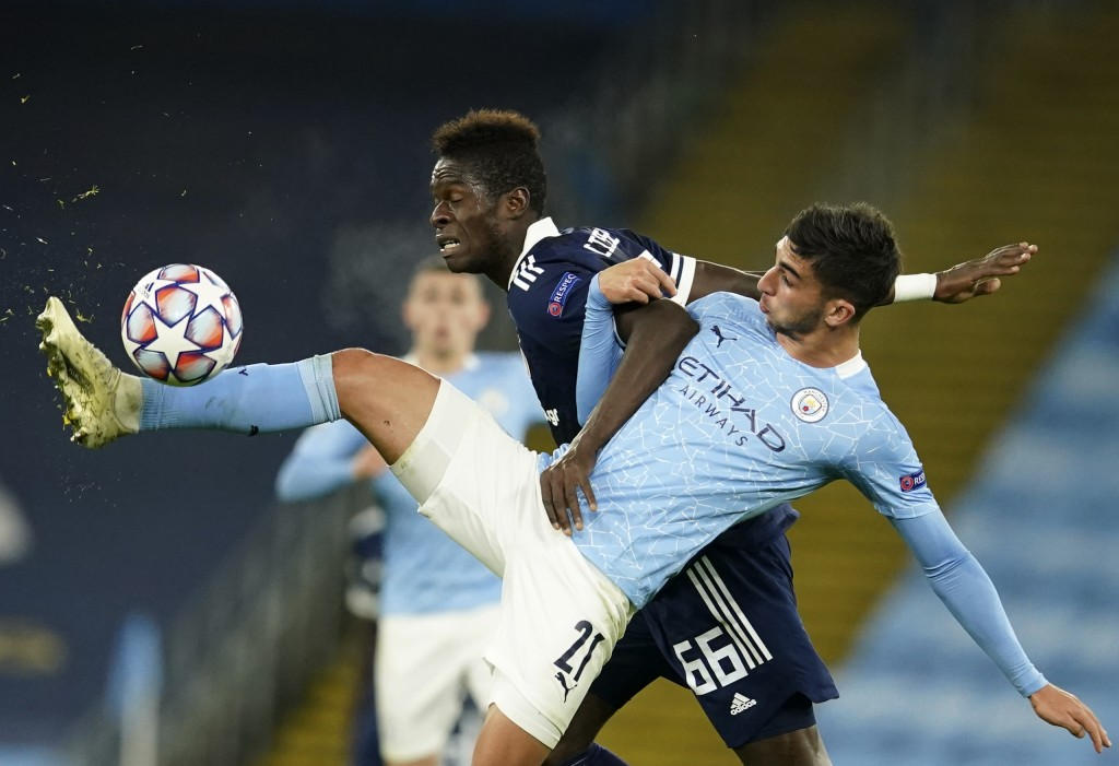Manchester City's Ferran Torres, front, duels for the ball with Olympiacos' Pape Abou Cisse during the Champions League group C soccer match between M...