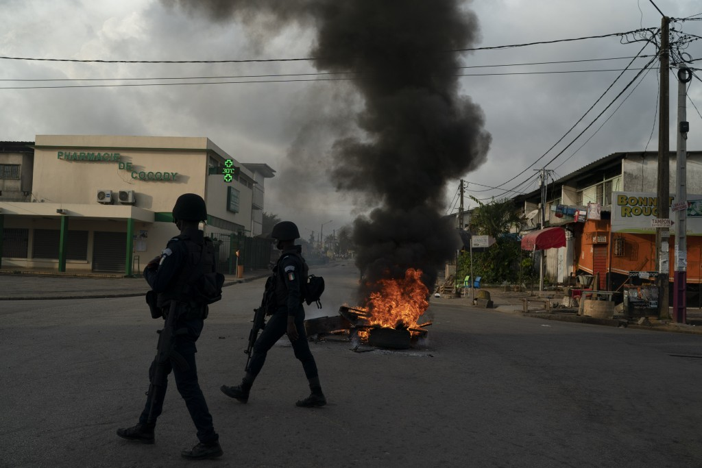 Policemen walk past a burning barricade during a protest after the security forces blocked the access to the house of the former president Henri Konan...