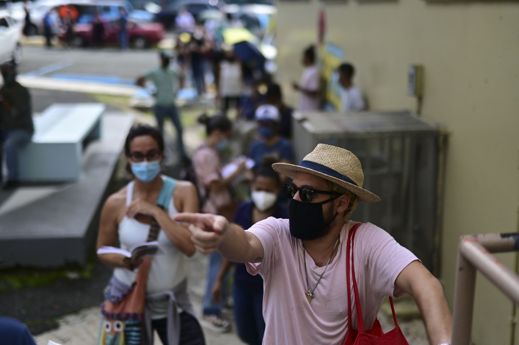 People wearing masks amid the COVID-19 pandemic wait in line to vote in the general election at a polling center set up at the Rafael Labra School in ...