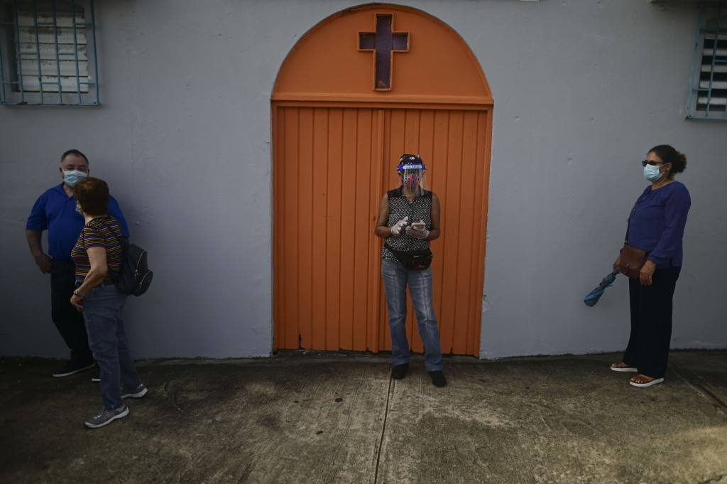 People practice social distancing amid the COVID-19 pandemic as they wait in line to vote for general elections, outside a church next door to the sch...