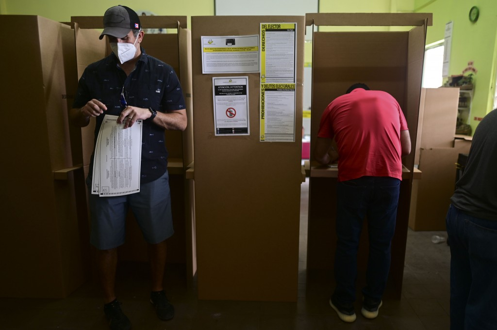 Voters use booths to mark their ballots for the general election at a polling center set up at the Rafael Labra School in San Juan, Puerto Rico, Tuesd...