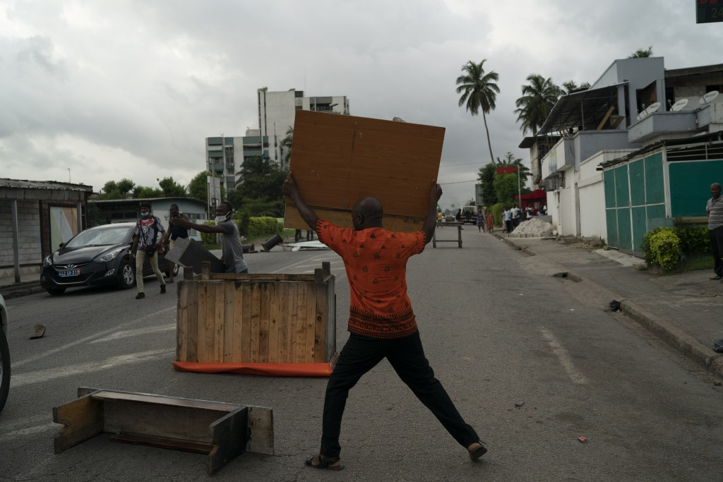 A supporter of the opposition parties throws a table on the street during a protest after security forces blocked the access to the house of the forme...