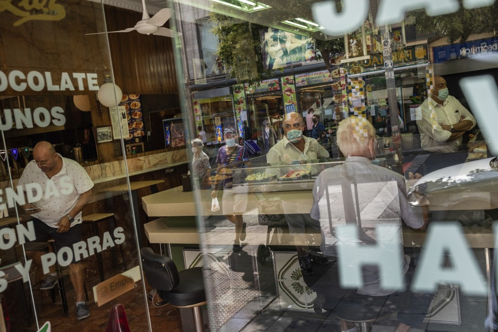 Waiters wearing face masks to prevent the spread of coronavirus talks work inside a bar in the southern neighbourhood of Vallecas in Madrid, Spain, We...