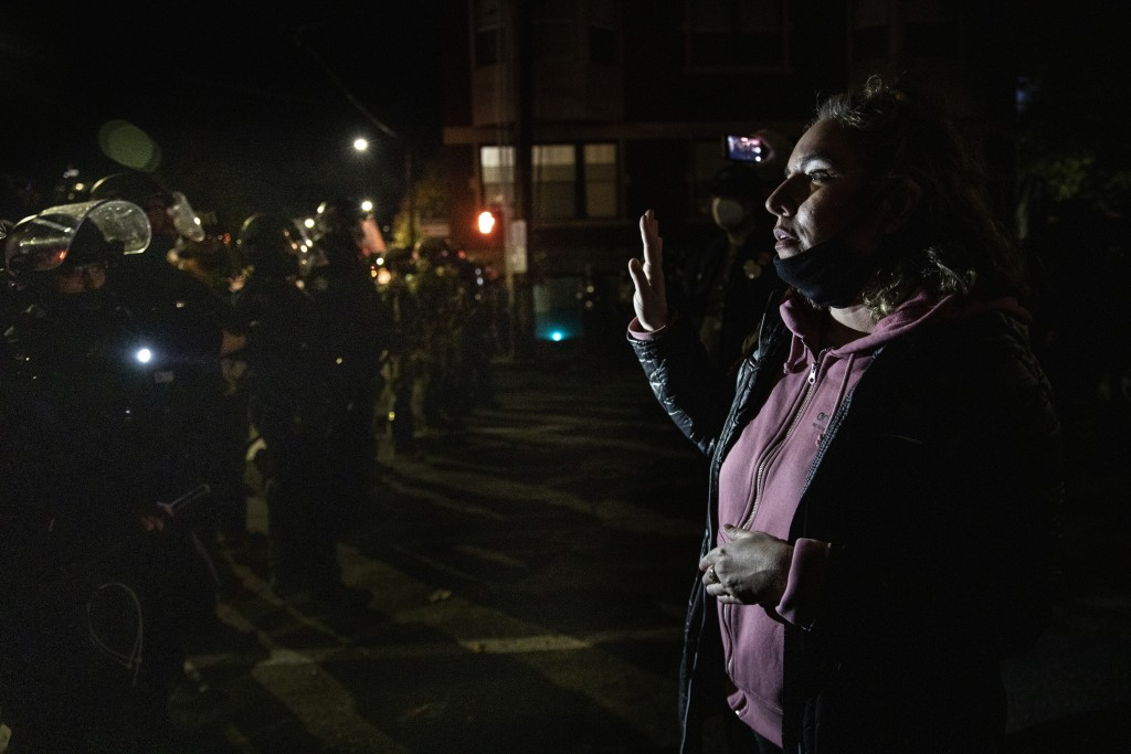 A protester confronts police during a march following Tuesday's presidential election in Portland, Ore. Wednesday, Nov. 4, 2020. (AP Photo/Paula Brons...