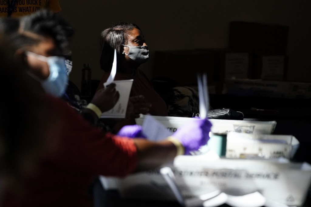 Election personnel examines a ballot as vote counting in the general election continues at State Farm Arena, Wednesday, Nov. 4, 2020, in Atlanta. (AP ...