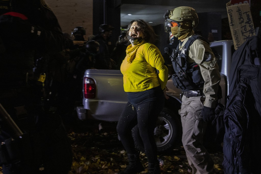 Police arrest a protester as clashes during a march following the presidential election Wednesday, Nov. 4, 2020, in Portland, Ore. (AP Photo/Paula Bro...