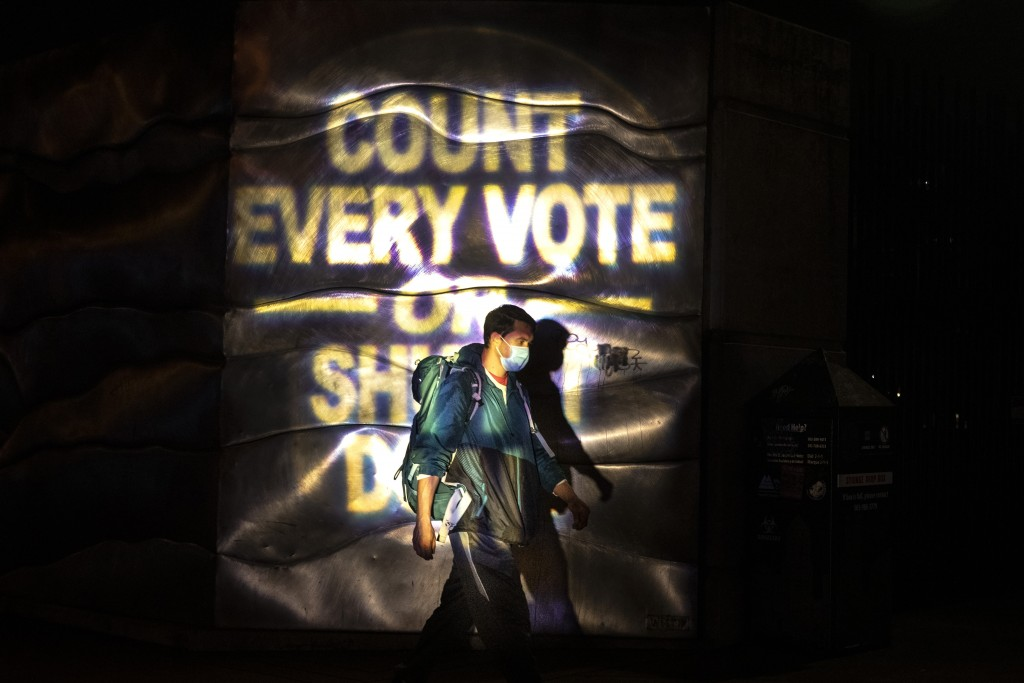 A man walks through a projected election slogan during protests following the Nov. 3 presidential election in Portland, Ore., Wednesday, Nov. 4, 2020....