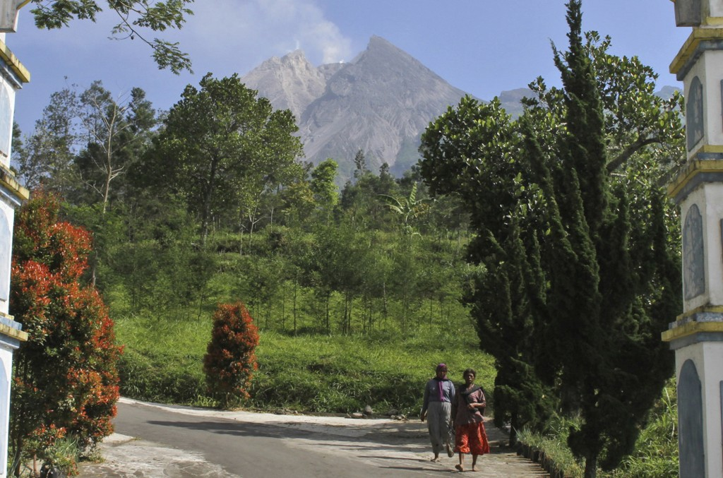 FILE - In this May 11, 2018, file photo, villagers walk along a road Mount Merapi is seen in the background in Pemalang, Central Java, Indonesia. Indo...