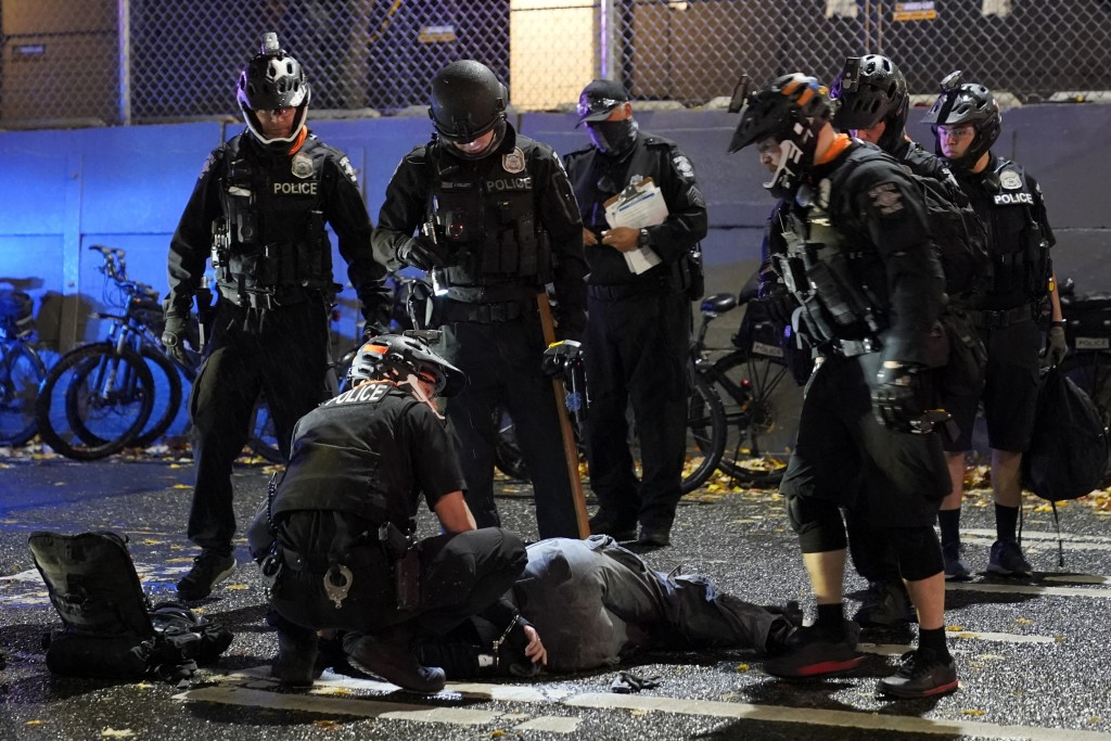 Police officials attend an injured man detained during a protest after the Nov. 3 elections in front of the east precinct station, Wednesday, Nov. 4, ...