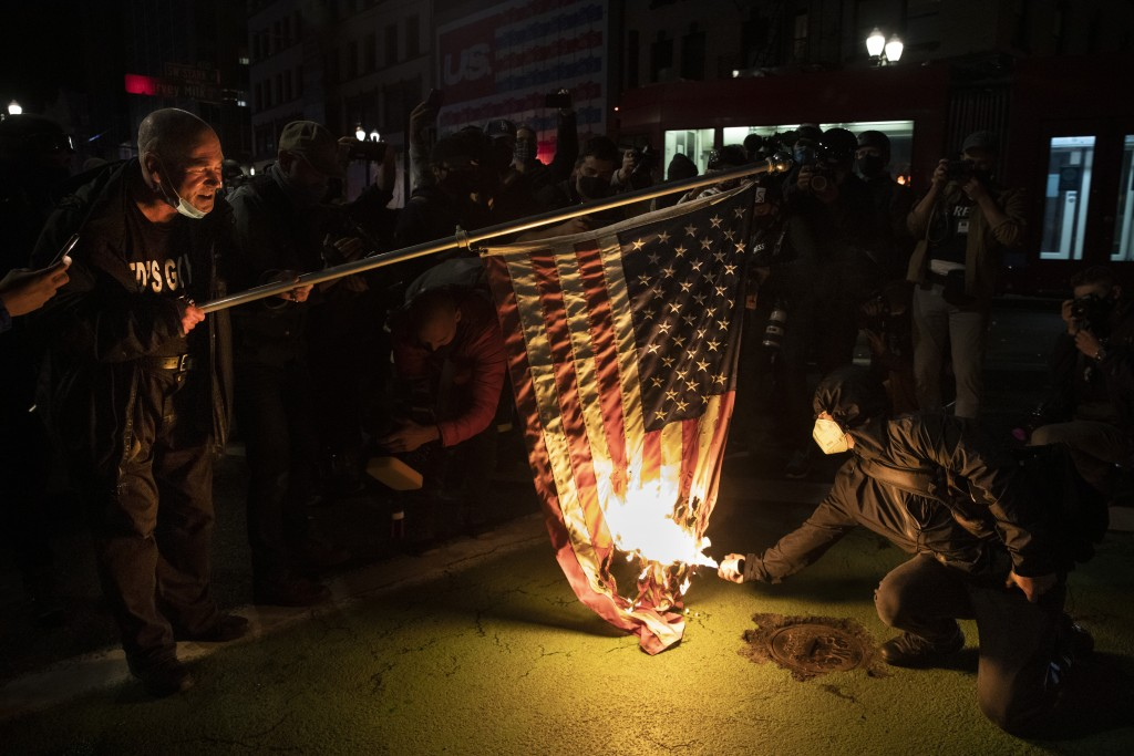 Protesters burn a national flag during a march following the presidential election Wednesday, Nov. 4, 2020, in Portland, Ore. (AP Photo/Paula Bronstei...
