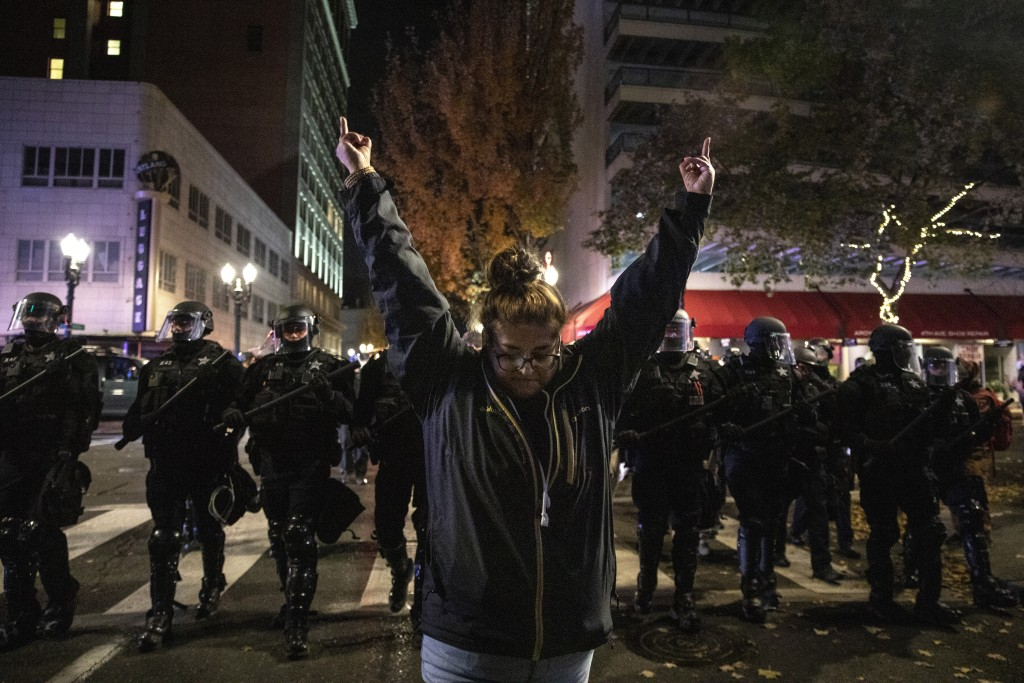 EDS NOTE: GRAPHIC CONTENT - A protester gestures in front of police during a march following Tuesday's presidential election in Portland, Ore. Wednesd...