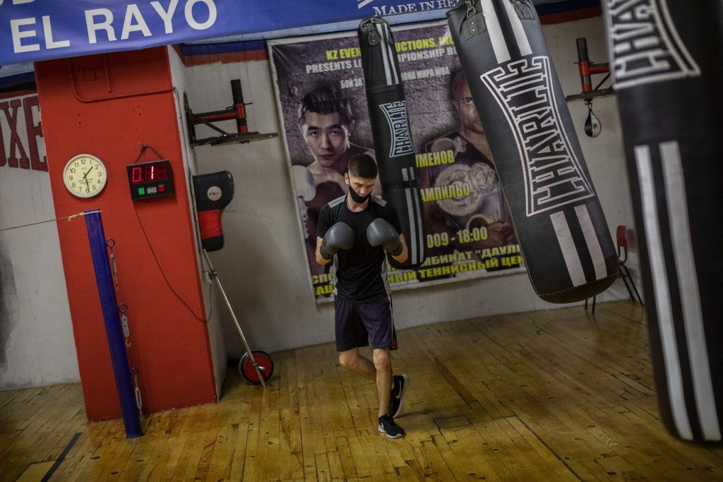 A man wearing face masks to prevent the spread of the coronavirus, exercises at a boxing gym in the southern neighbourhood of Vallecas in Madrid, Spai...