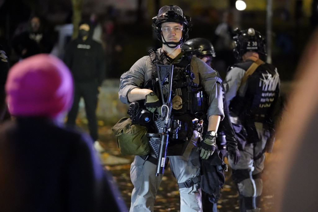 A police official looks on during a protest after the Nov. 3 elections, Wednesday, Nov. 4, 2020, in Seattle. (AP Photo/Ted S. Warren)
