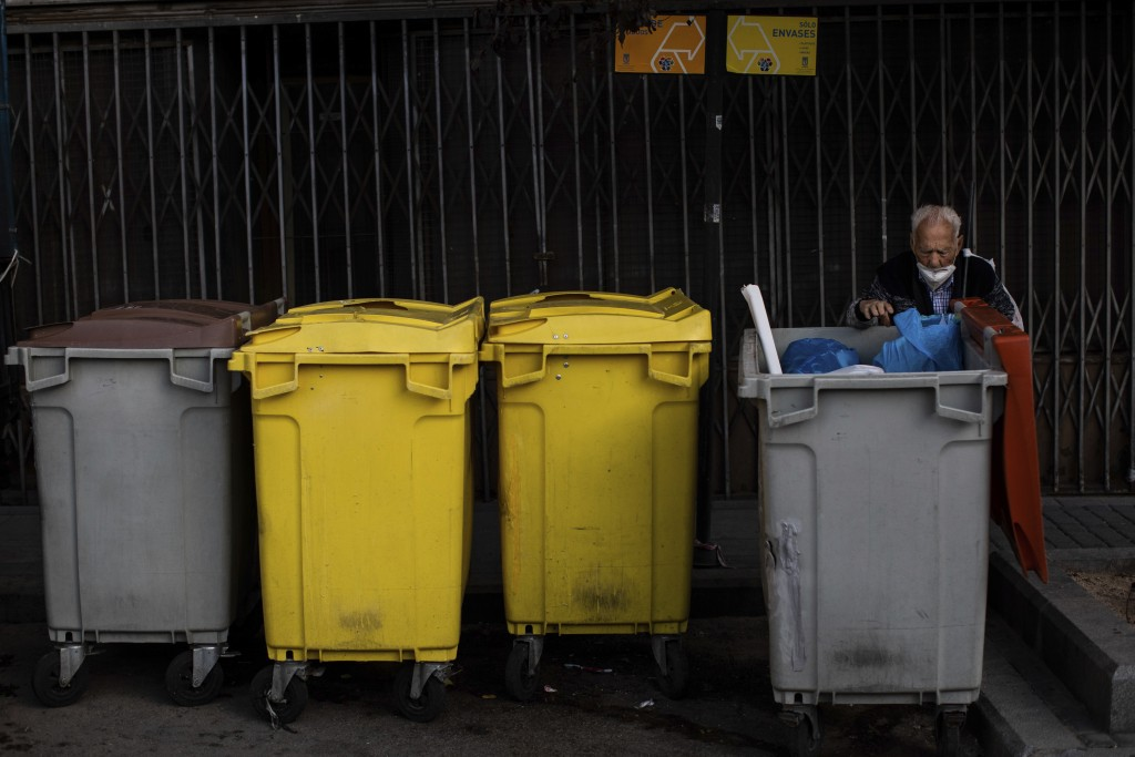 An elderly man searches through garbage bins in the southern neighbourhood of Vallecas, Madrid, Spain, Thursday, Oct. 1, 2020. Spain's government expe...