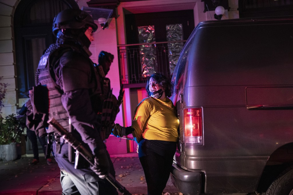 Police arrest a protester as clashes during a march following the presidential election Wednesday, Nov. 4, 2020, in Portland, Ore.  (AP Photo/Paula Br...
