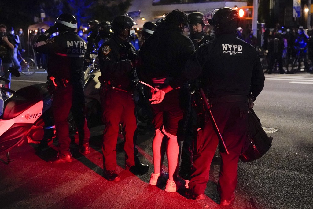New York Police officers talk with people arrested during a demonstration, Wednesday, Nov. 4, 2020, in New York. (AP Photo/Seth Wenig)