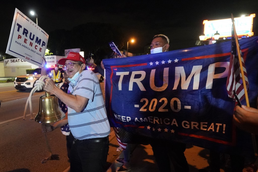 In this Nov. 3, 2020, photo, Rafael Fagundo rings a bell as he and other supporters of President Donald Trump chant and wave flags outside the Versail...