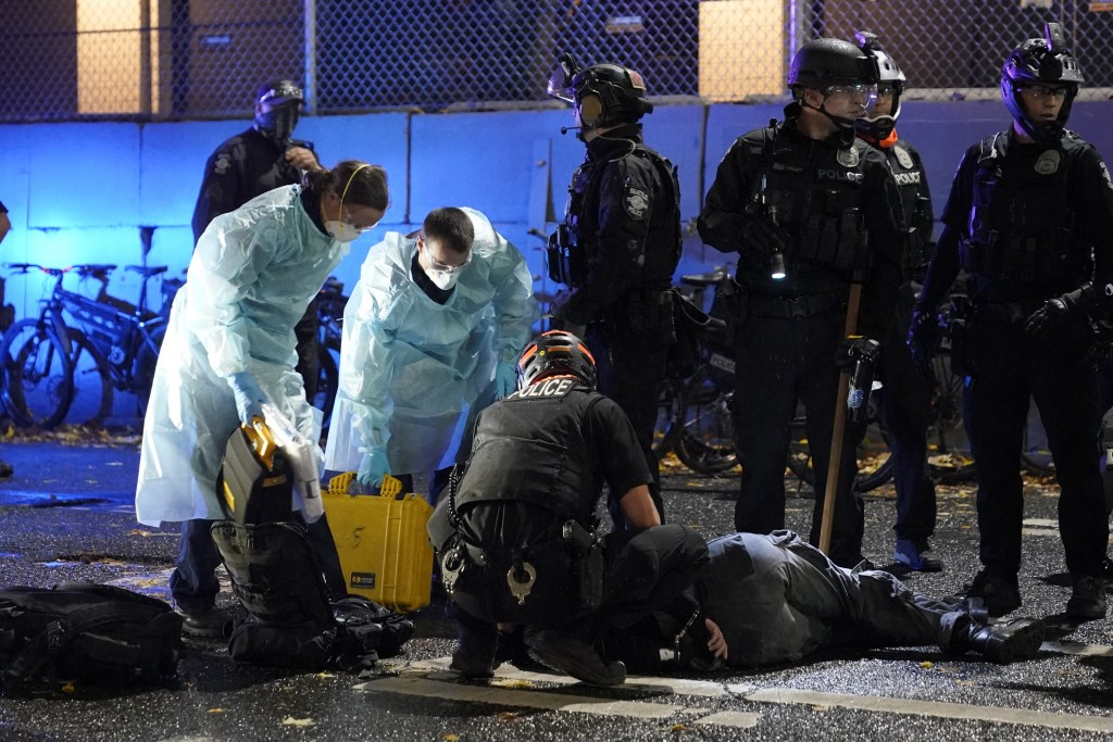 Emergency crews attend an injured man detained by police during a protest after the Nov. 3 elections in front of the east precinct station, Wednesday,...