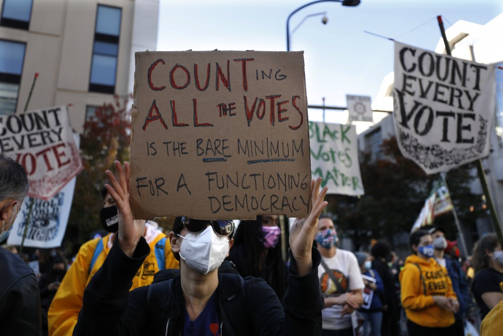 Demonstrators hold signs that urge all votes be counted outside the Pennsylvania Convention Center where votes are being counted, Thursday, Nov. 5, 20...