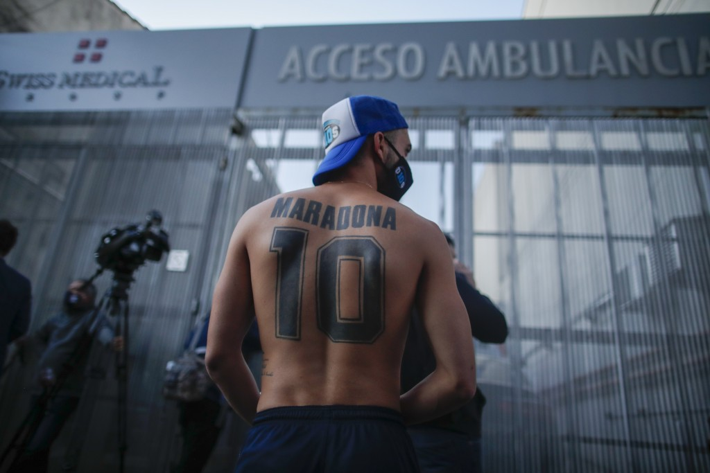 Soccer fans gather outside Clinica Olivos where former soccer star Diego Maradona will undergo surgery, in Buenos Aires, Argentina, Tuesday, Nov. 3, 2...