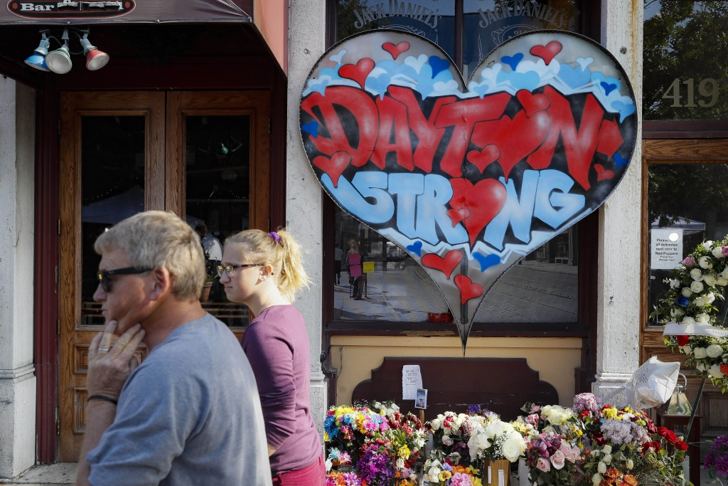 FILE - In this Aug. 7, 2019, file photo, pedestrians pass a makeshift memorial for the slain and injured victims of a mass shooting that occurred in t...
