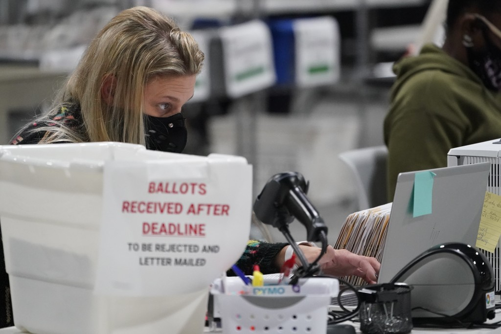 Officials work on ballots at the Gwinnett County Voter Registration and Elections Headquarters, Friday, Nov. 6, 2020, in Lawrenceville, near Atlanta. ...