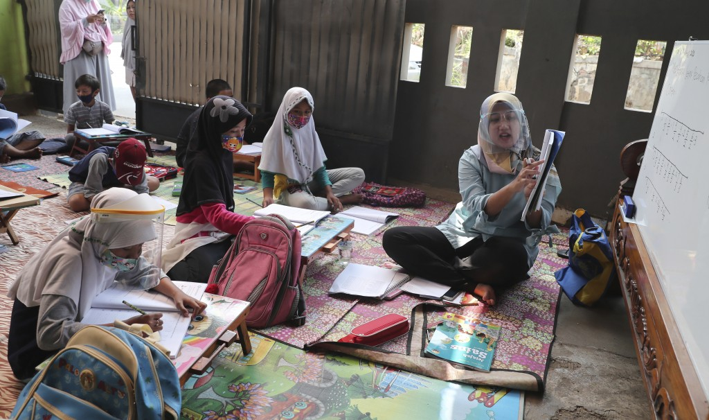 Stock image of Indonesian teacher instructing makeshift class for students at her residence in Tangerang, Indonesia.