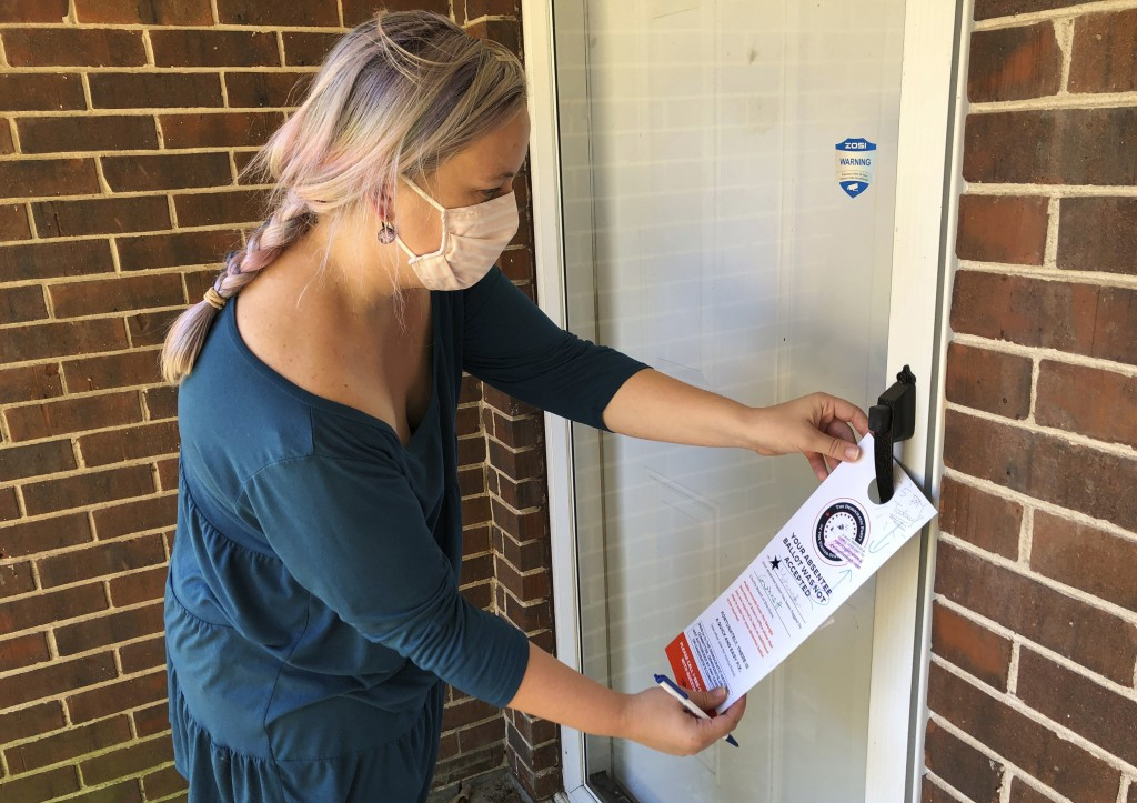 Christin Clatterbuck leaves an affidavit and information about fixing absentee ballots on the door of a home in Stone Mountain, Ga., Friday, Nov. 6, 2...